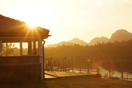 Sunset over the fjord in Norway, a gazebo lit by the rays of the sun, in the distance mountains.