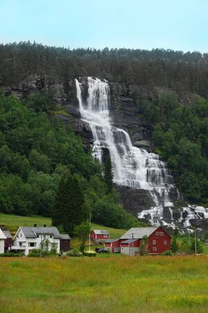 Travel to Norway, a large waterfall flows down from the mountain, near a settlement of several bright houses.