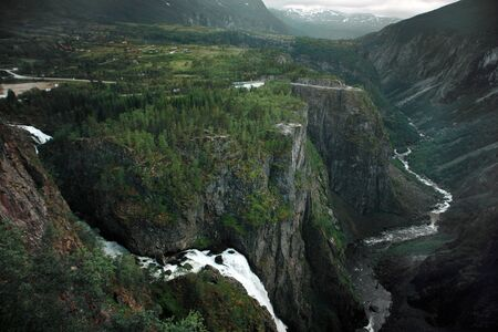 Travel to Norway, waterfalls flow from the mountains into the river at the bottom of a large canyon, top view. Standard-Bild