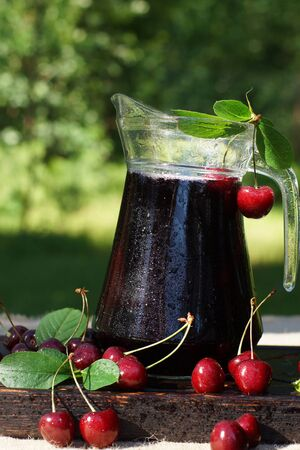 Jug with cold cherry juice, covered with droplets, next to a sweet cherry with leaves.