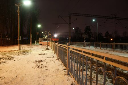 The train station at the station fenced with metal bars in the winter, the train arrived and stands on rails.
