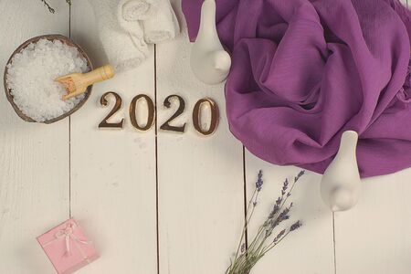 SPA set and golden numbers 2020 on a white plank background with a purple cloth