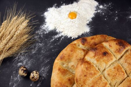 Two pita breads with a golden crust lie on a table next to flour, a spikelet of wheat and quail eggs