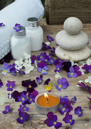 Burning candle in the middle of purple pansy flowers and a spa set with skin lotion.