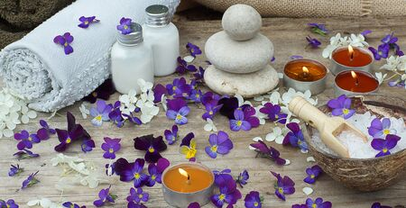Set for spa treatments with bath salt, stones for hot massage and skin lotions in the midst of small purple flowers of pansies.