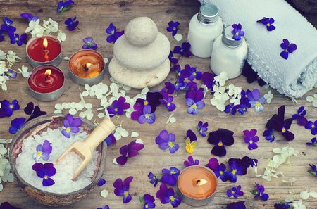 Burning candles and spa set with bath salt, stones for hot massage and skin lotions in the midst of small purple flowers of pansies.