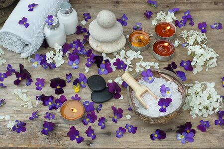 Burning candles and spa treatment kit with bath salt, stones for hot massage and skin lotions in the middle of purple flowers of pansies. Stock Photo