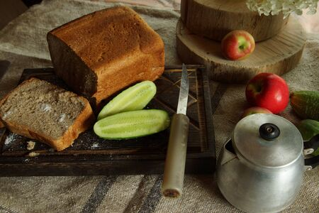 Still life with fresh bread and salt, next to a green cucumber from the garden, rustic style.