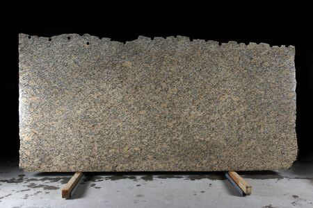 A large slab of natural yellow stone with dark dots called granite Phoenix Yellow. Banco de Imagens