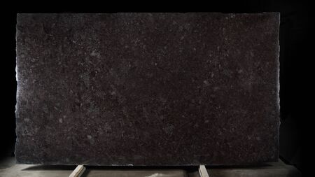 A large slab of natural stone of brown color with shiny scales called granite Brown Antique.