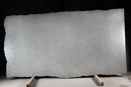 A large slab of natural gray stone with dark dots is called granite Bianco Cristall.