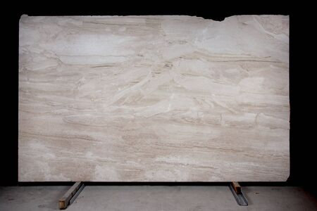 A large slab of natural stone in beige color, with stains and spots called marble Breccia Sarda.