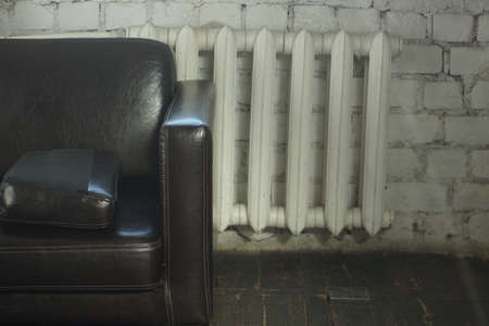 A large brown leather sofa stands in a room with a white brick wall near the radiator.