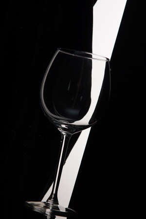 Empty wine glass bent over black and white background.