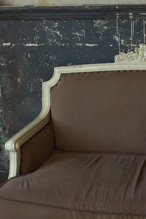 Part of a beautiful antique sofa that stands against the wall.