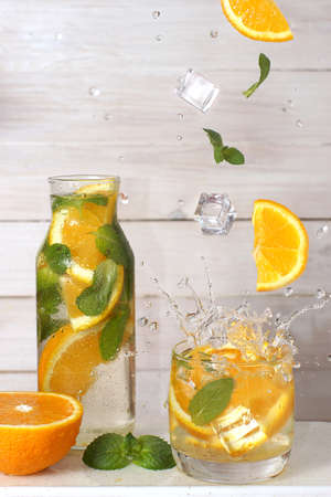 Lemonade or cocktail with orange and mint in a bottle and glass in the kitchen, ingredients levitation. Imagens