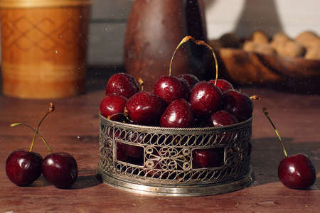 Cherry berries in a beautiful carved bowl on a table with water droplets.