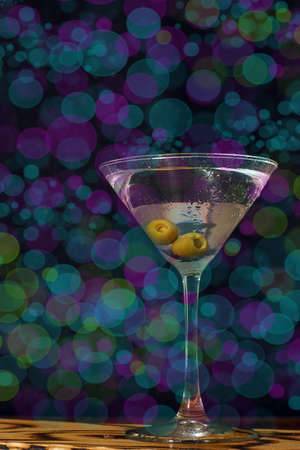 Glass of martini with olive on the background of bright lights in the bar Imagens