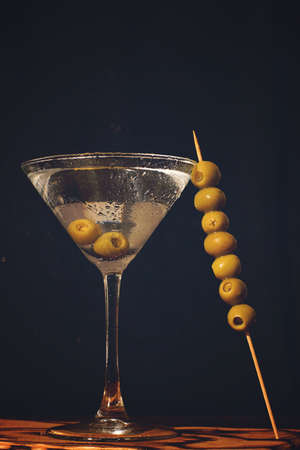 Martini glass and stick with olives on a dark background in a bar Imagens