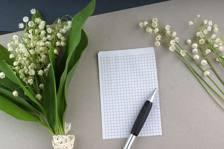 Top view of a piece of paper and a pen lying next to a beautiful bouquet of white lilies of the valley
