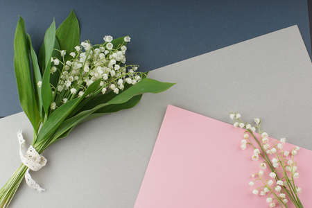 Top view of a beautiful bouquet of white lilies of the valley lying on a table on multicolored cardboard paper