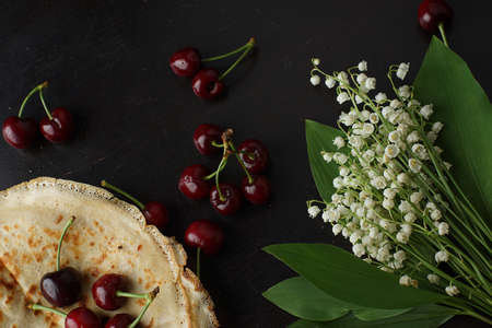 Russian flat pancakes are stacked on top of cherries and next to them are a bouquet of white lilies of the valley on a dark table.