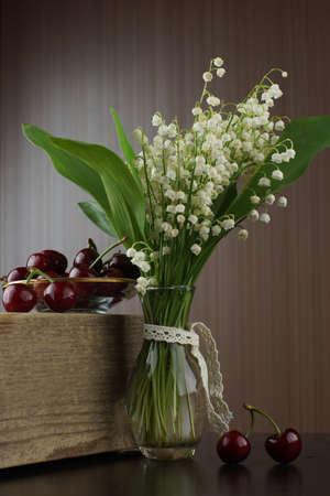 A bouquet with lilies of the valley stands in a transparent vase with an overnight stay next to it on a wooden board low with red cherries. Imagens