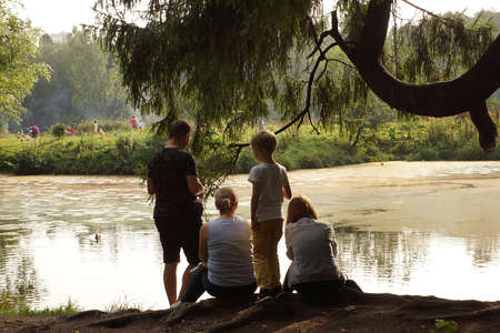 A family of four settled down by the lake in the park