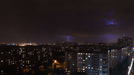 Strong thunderstorm with lightning on the background of the city at night