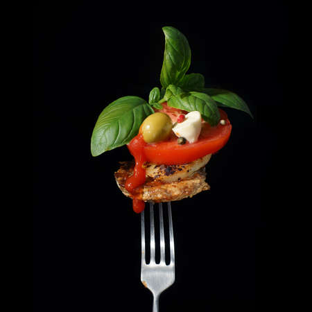Cutlet on a fork with a tomato mozzarella and basil a drop of ketchup on a dark background