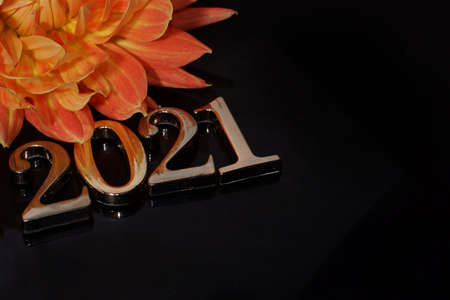 Inscription 2021 lined with metal numbers at an angle to the red of a beautiful dahlia flower