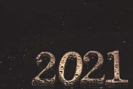 Metallic numbers 2021 in golden color covered with water droplets on a dark background