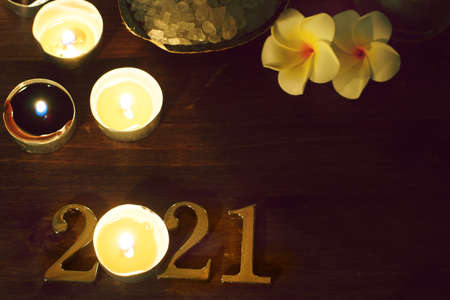 Spa composition with numbers 2021 burning candles and plumeria flowers Imagens