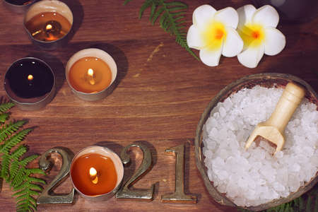 Top view of spa composition with white sea salt plumeria flowers and numbers 2021 illuminated by burning candles Imagens