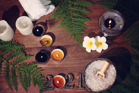 Set for spa treatments on a wooden table with burning candles flowers, numbers 2021 and a fern