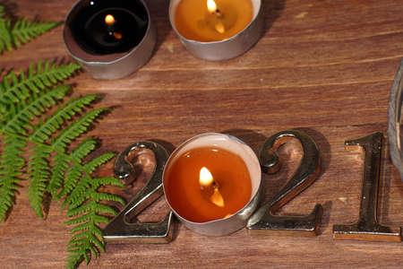 Burning candle figures 2021 and fern on wooden background