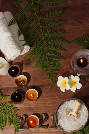 Golden numbers 2021 of a burning candle and a set for spa treatments with white sea salt on a wooden table