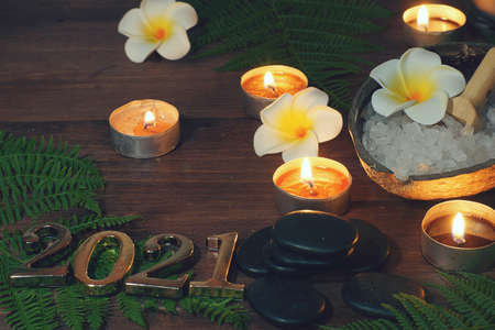 Metal numbers 2021 next to burning candles, stones for hot massage and fern on a wooden table