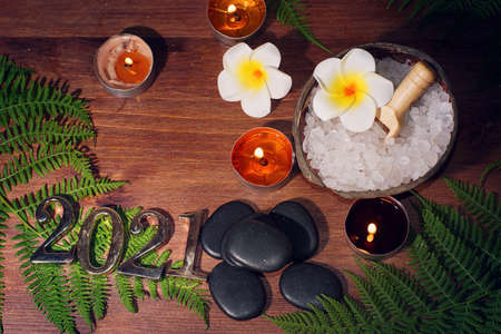 Basalt black stones for hot massage, sea salt for peeling, burning candles and 2021 numbers on the table Imagens