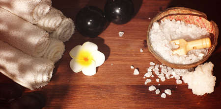 Set for spa treatments and hot massage stones with white plumeria flower on wooden background Imagens