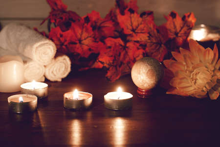 Autumn leaves and burning candles in spa composition