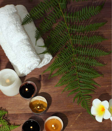 spa composition with fern candles and plumeria flowers on wooden background