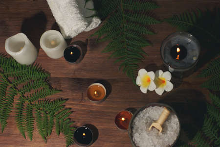 Spa composition with burning candles, plumeria flowers and fern leaves on wooden background Imagens