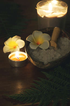 Dark spa set with burning candles of plumeria flowers white and green fern Imagens