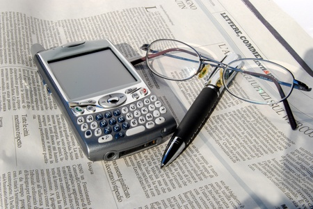 Smartphone, cell phone, pen and glasses. A smartphone is a mobile phone offering advanced capabilities beyond a typical mobile phone, often with PC-like functionality photo