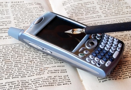 Smartphone and pen over old book. A smartphone is a mobile phone offering advanced capabilities beyond a typical mobile phone, often with PC-like functionality photo
