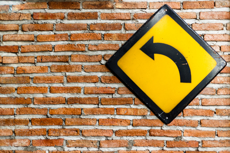 turn left sign: Brick wall with turn left sign Stock Photo