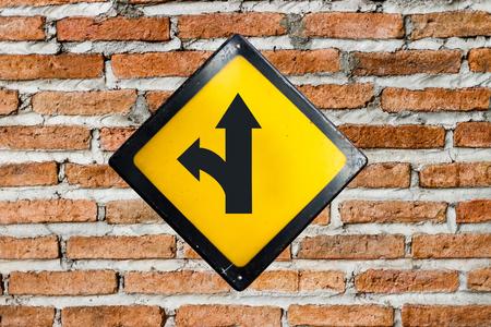 turn left sign: left turn split sign on brick wall