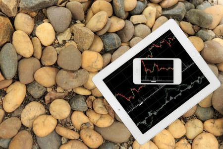 computer devices: Smartphone and tablet with graph on stone floor Stock Photo