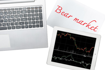 bear market: Computer, paper with bear market text and tablet with graph is isolated on transparent Stock Photo